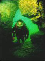 Diver underwater in cave opening
