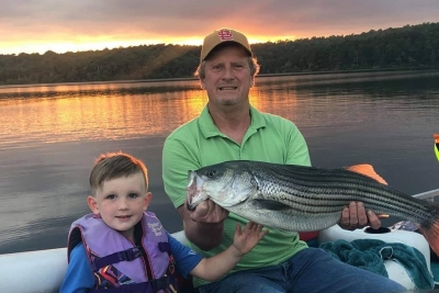 Father and son with Norfork Lake striper