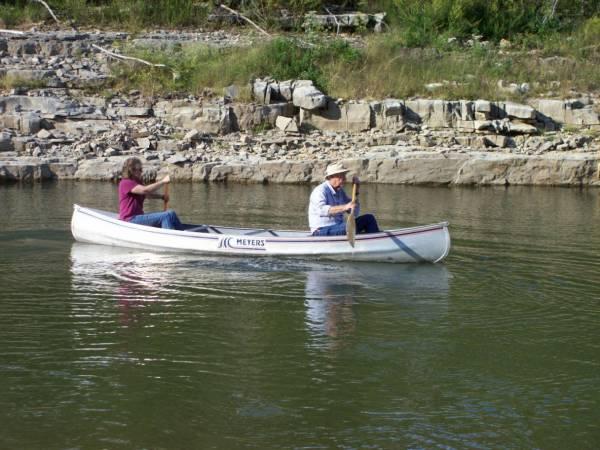 Man and woman canoe on Norfork Lake