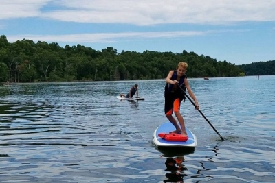 Boy paddle boards on lake