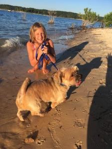 Girl and dog on Norfork Lake sandy beach