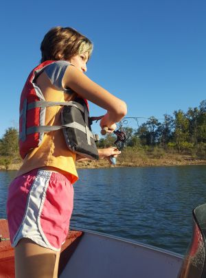 Girl fishing from boat on Norfork Lake
